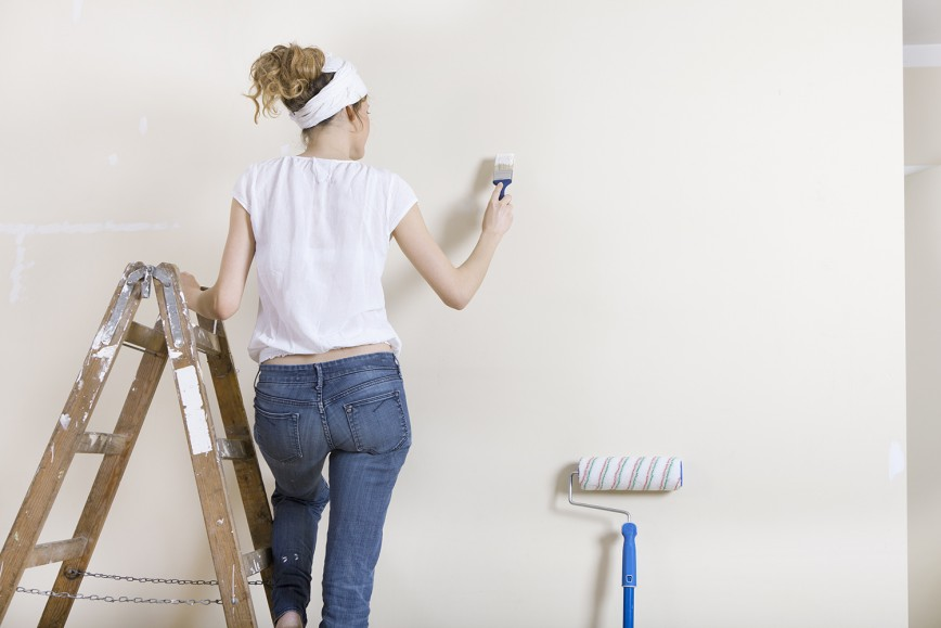 Women painting wall white