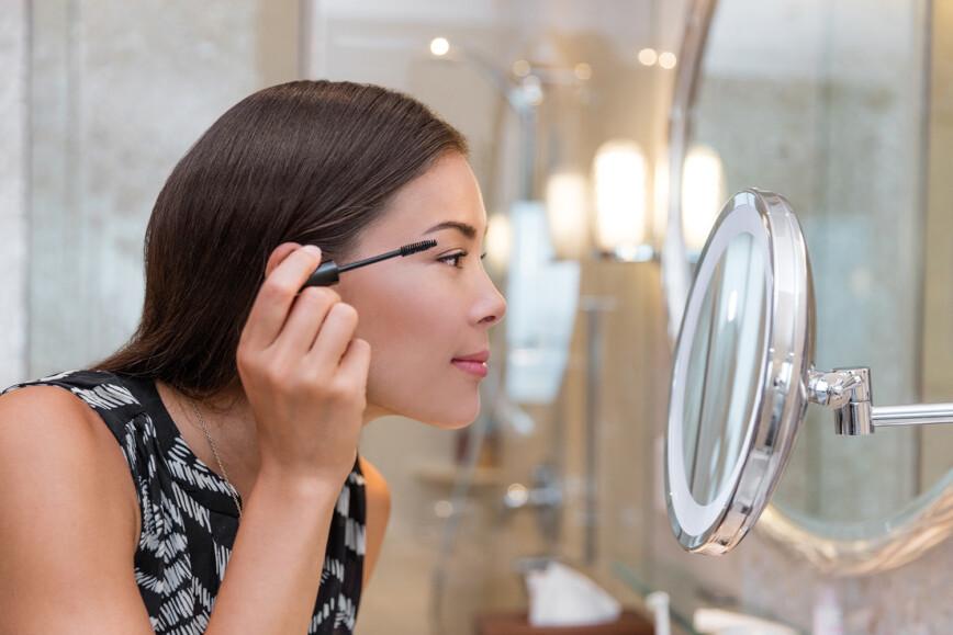 Round light Vanity Mirror, Makeup Mirror. Women putting on mascara