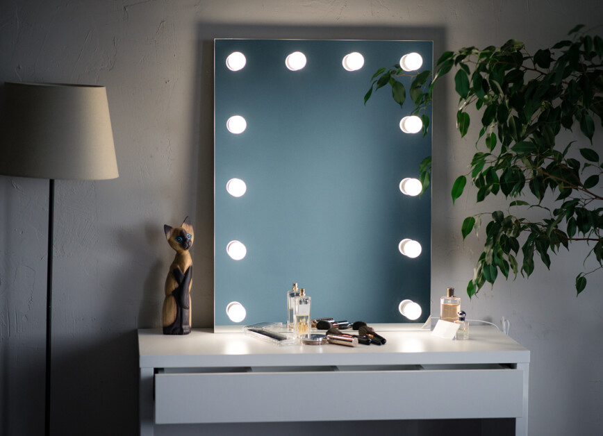 makeup mirror and cosmetics in the white dressing room with a tree and floor lamp