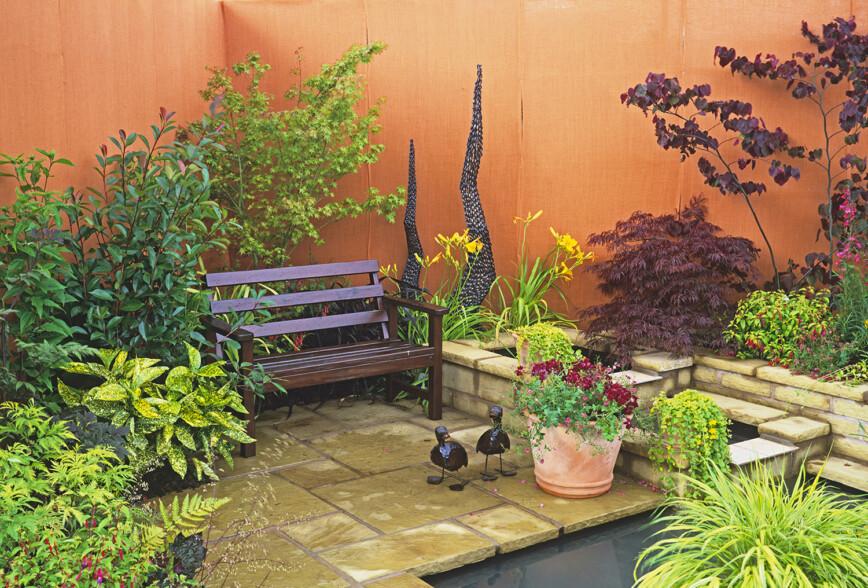 Water feature in orange walled garden with wooden bench