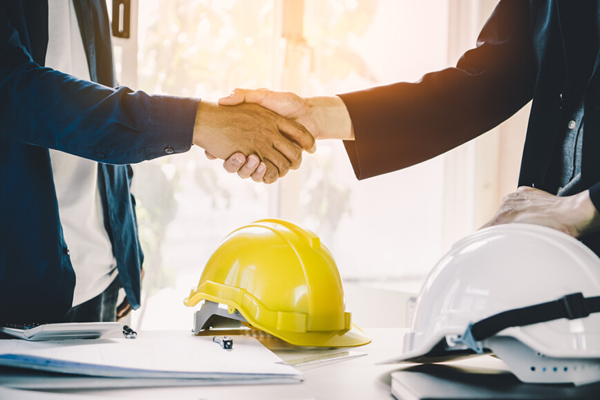 Shaking hands, hard hats and contracts