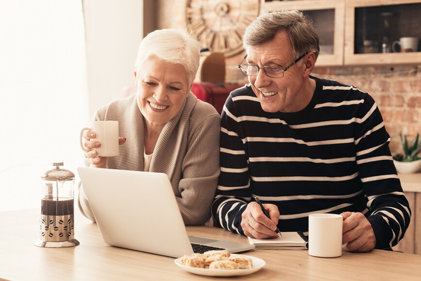 Elderly couple sat at table looking at laptop with drink and biscuits