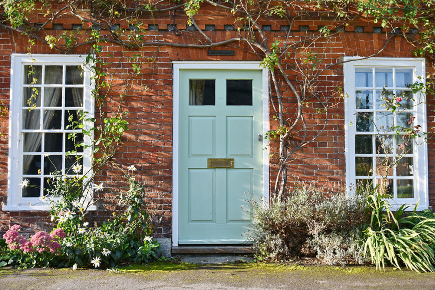 Cute cottage with pale green painted door.