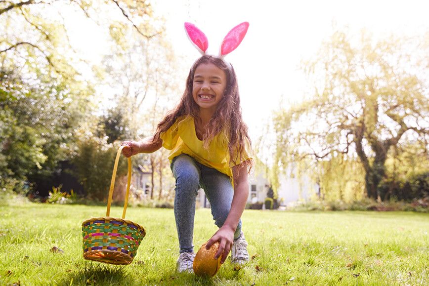 Chocolate Easter Egg hunt with child with rabbit ears and basket