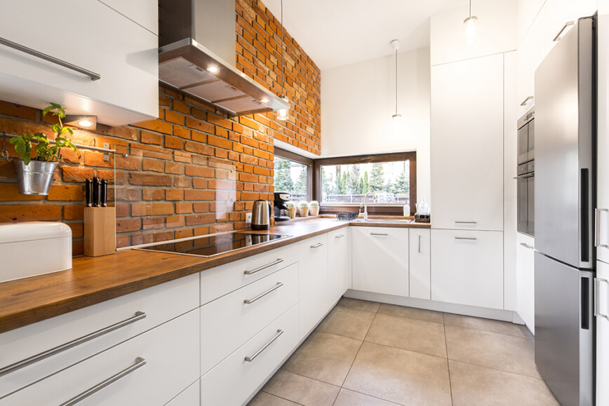 Modern white kitchen with bare brick walls, under cupboard lighting and tiled floor