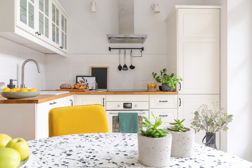 White kitchen with bright yellow accent chair