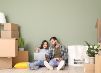Young couple with cardboard boxes for moving home and laptop