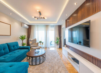 Modern contempory louge with seventies vibe. Blue corner sofa with wide screen TV and wood paneled walls