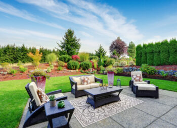 Large garden with lawn and specialist patio design, with garden furniture. Garden surrounded by trees