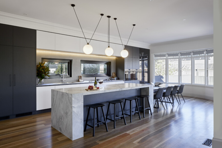 Modern streamlined kitchen with giant island with dining area by Mint