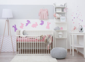 Babies bedroom with white wooden cot and rabbit animal wall stickers