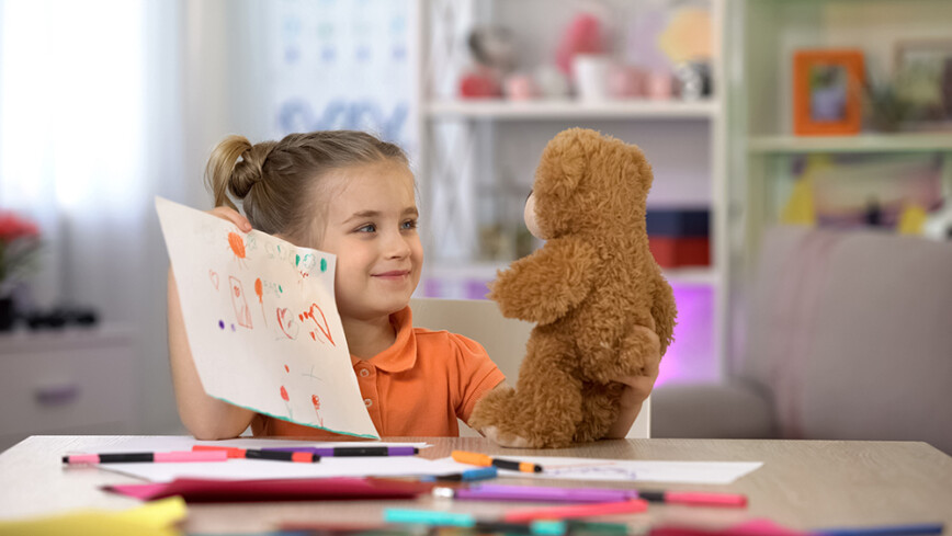 Smilling girl with teddy bear. Showing her drawing skills