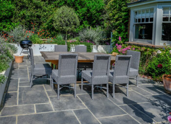 Patio garden with wooden table and grey wicker chairs