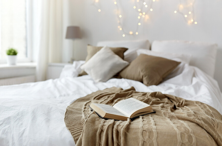 Peaceful bedroom with white bedding and brown sheet. Plus fairy lights