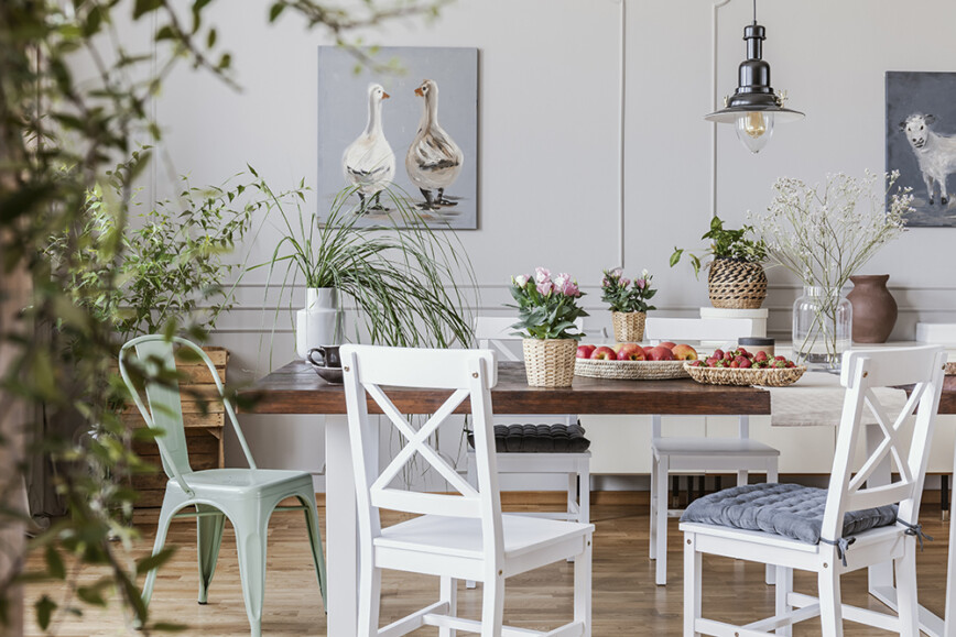 Dining room with white wooden dining table and chairs, goose painting and plants