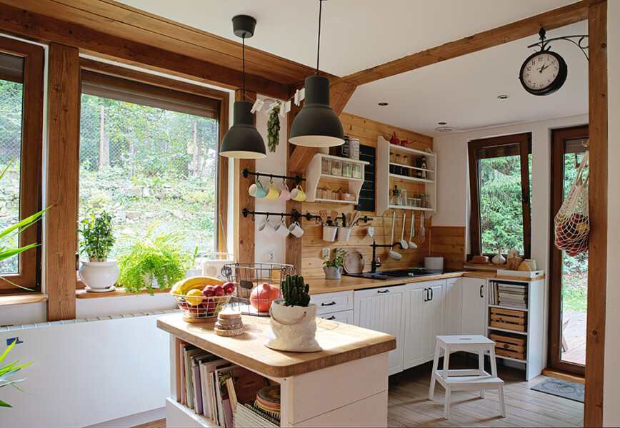Cottage interior. Country kitchen with white kitchen cupboards and large kitchen island