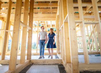 Man and women standing within the wooden shell of a new build home
