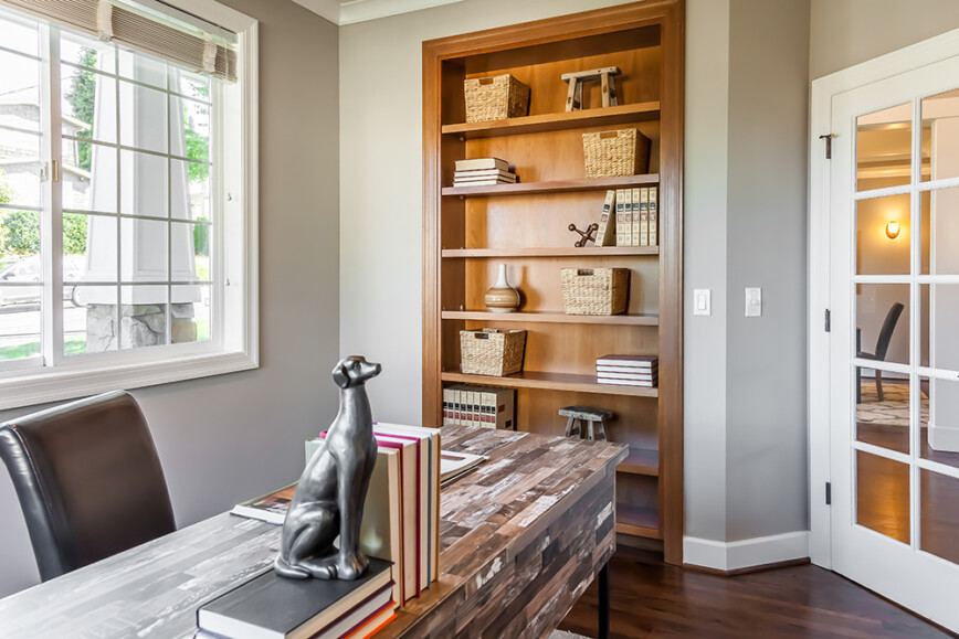 Traditional solid wood bookcase built into wall of office.