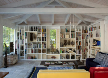 White wooden living room with beamed ceiling and large bookcase