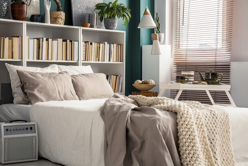 White bookcase behind bed in bedroom